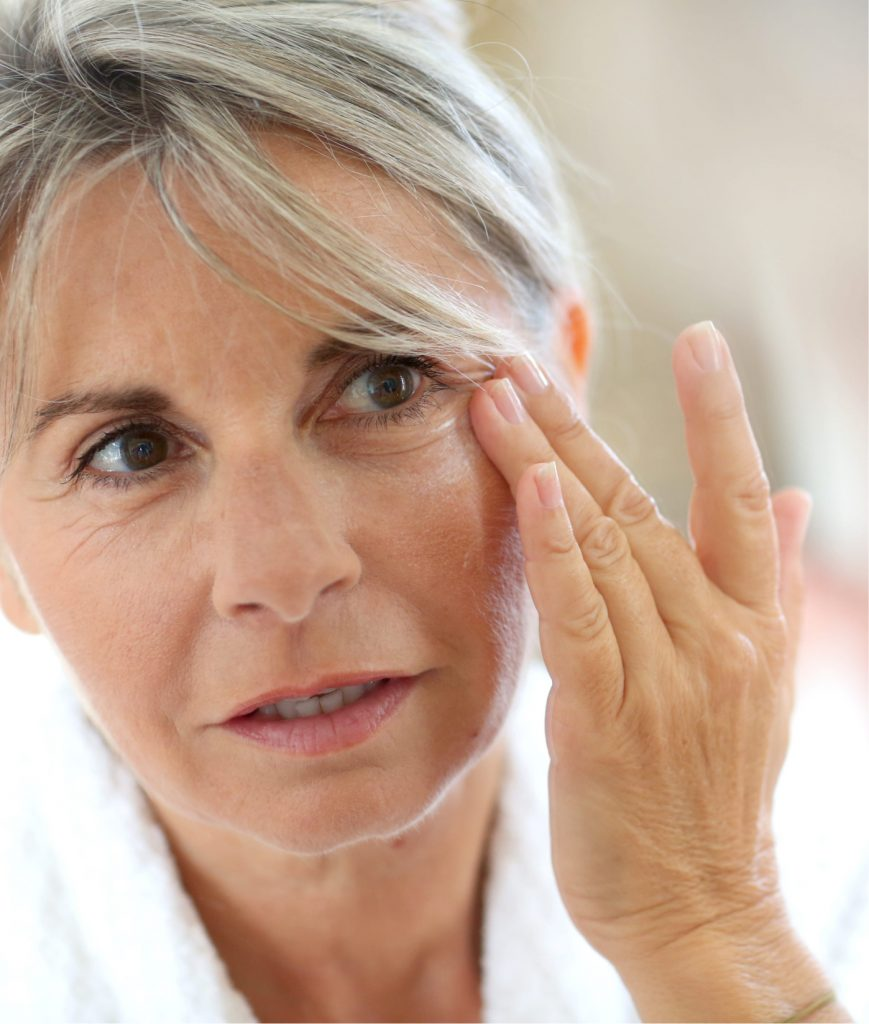Older woman inspecting the wrinkles around her eyes